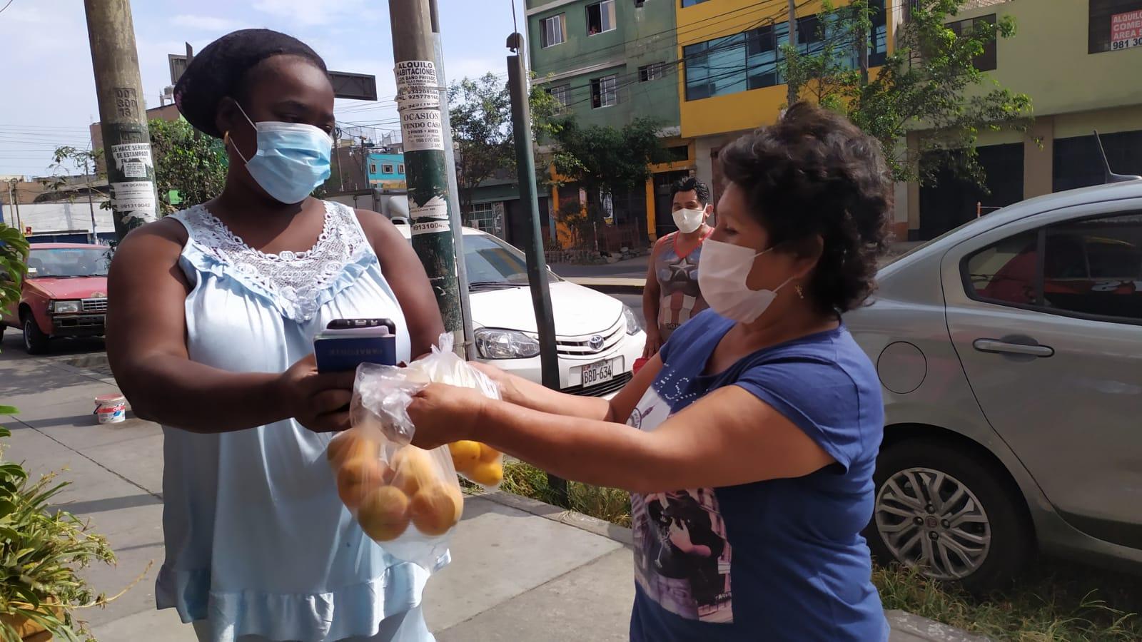 Alicia entrega a Yuneikys una bolsa con frutas. Una muestra de solidaridad en tiempos de aislamiento. Foto: Luis Enrique Pérez / Convoca.pe